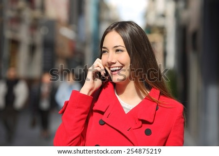 Cheerful woman talking on the phone in the street wearing a red jacket - stock photo