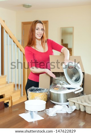 Cheerful woman unpacking new crock-pot at home