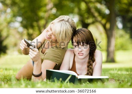 Cheerful woman using cellphone while her friend reads a book - stock photo