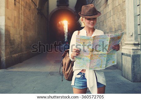 Cheerful woman wanderer with trendy look searching direction on location map while traveling abroad in summer, happy female tourist searching road to hotel on atlas in a foreign city during vacation - stock photo