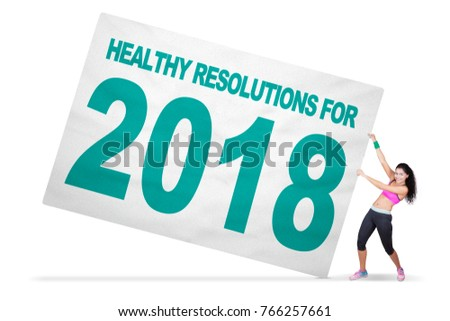 Cheerful woman wearing sportswear while pulling a text of healthy resolutions for 2018 on the banner