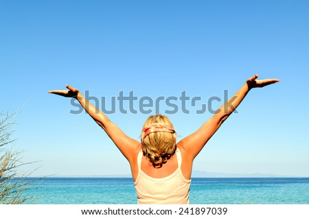 Cheerful woman with arms raised to the sky near the sea - stock photo