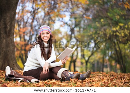 Cheerful woman with book in autumn park, smiling and looking at camera