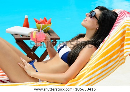 Cheerful woman with drink and sunglasses . She is sunbathing and relaxing at the poolside with a book and fruit in a table. - stock photo