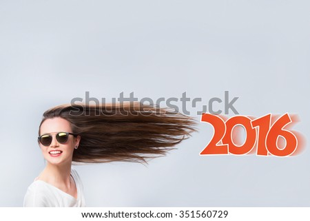 Cheerful woman with hair in the wind. Background of the text in 2016. - stock photo