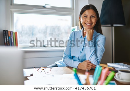 Cheerful woman with hand on chin wearing blue shirt while seated at desk covered with papers, coffee and eyeglasses and window in background - stock photo