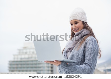 Cheerful woman with winter clothes on using her laptop outdoors on a cold grey day - stock photo