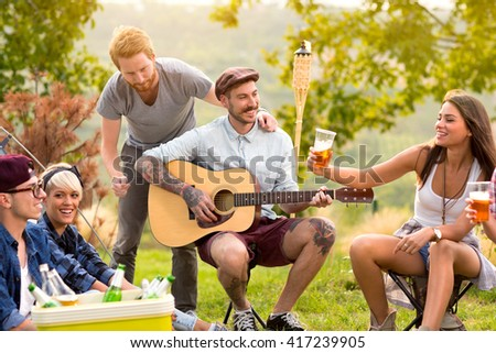 Cheerful women and male enjoying with beer in camp in wood - stock photo
