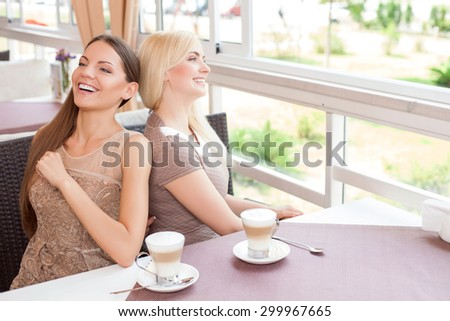 Cheerful women are resting together in cafe. They are sitting at the table and leaning on each others back. One girl is tickling another woman secretly. They are smiling - stock photo