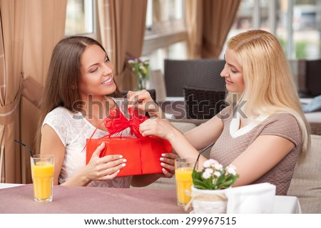 Cheerful women are sitting in cafe. The brunette girl is holding a gift and looking at her friend mysteriously. The blond lady is opening the gift with interest. They are smiling with joy - stock photo