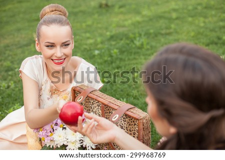 Cheerful women are sitting on green grass near a basket of food and flowers. The blond lady is giving an apple to her friend. She is looking at her with joy and smiling - stock photo
