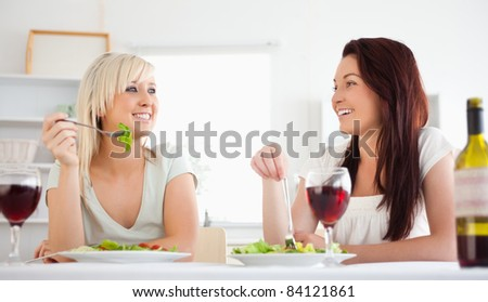 Cheerful women eating salad in a dining room - stock photo