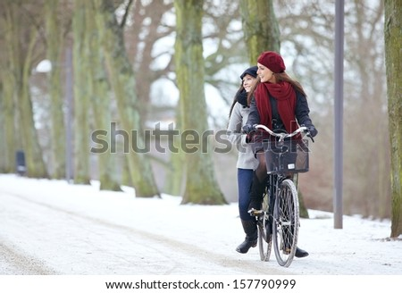 Cheerful women enjoying the beauty of the park by riding a bike together - stock photo