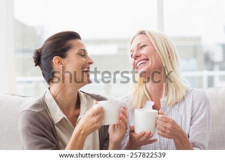 Cheerful women gossiping while having coffee in living room - stock photo