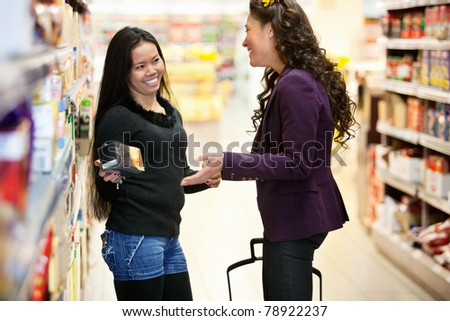 Cheerful women having conversation in shopping centre while holding product - stock photo