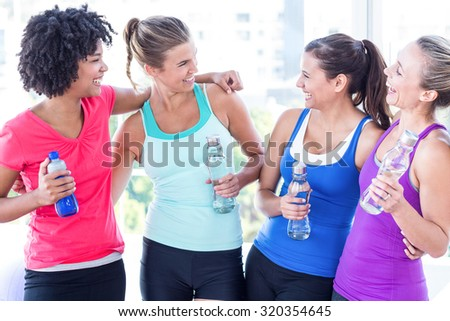 Cheerful women holding water bottle and smiling in fitness studio - stock photo