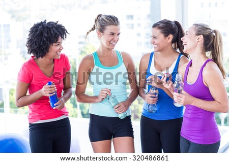 Cheerful women holding water bottle in fitness studio - stock photo