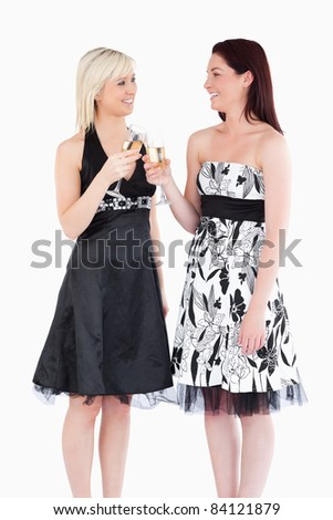 Cheerful women in beautiful dresses toasting with champaign in a studio