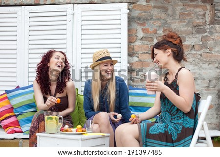 Cheerful women in outdoor cafe  - stock photo