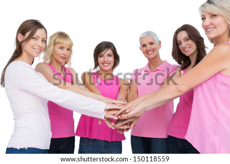 Cheerful women posing in circle holding hands looking at camera  wearing pink for breast cancer on white background - stock photo