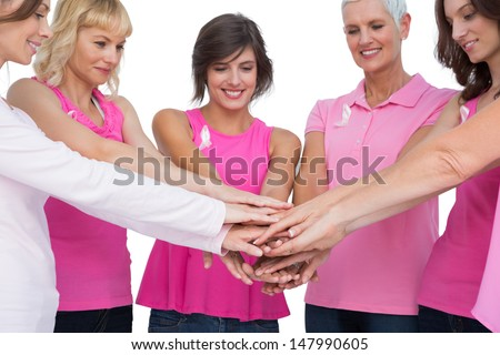 Cheerful women posing in circle holding hands wearing pink for breast cancer on white background