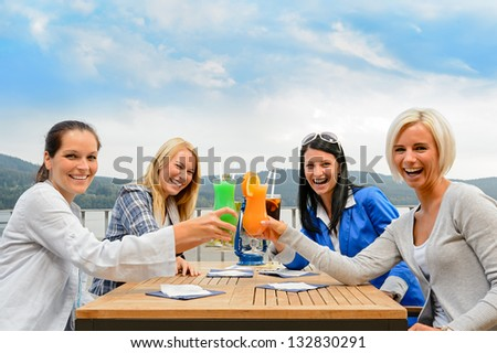 Cheerful women toasting with cocktails at outdoor restaurant summer terrace - stock photo