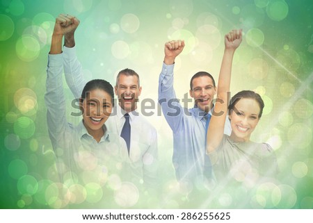 Cheerful work team posing with hands up against green abstract light spot design - stock photo