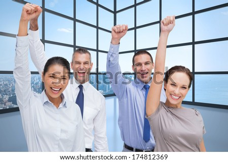 Cheerful work team posing with hands up against room with large window showing city - stock photo