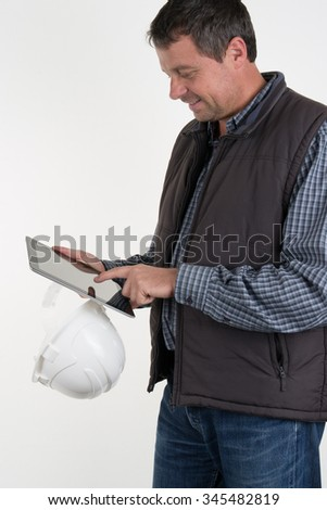 Cheerful worker in white helmet and brown waistcoat holding shockproof digital tablet in both hands.  - stock photo