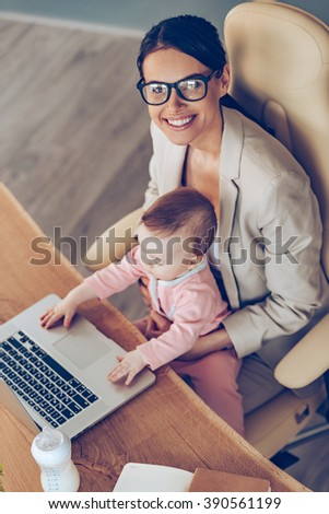Cheerful working mother. Top view of young beautiful businesswoman looking at camera with smile while sitting with baby girl on her knees at her working place - stock photo