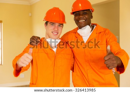 cheerful workmen giving thumbs up inside house  - stock photo