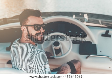 Cheerful yacht owner. Smiling young man holding hand on steering wheel while driving yacht - stock photo