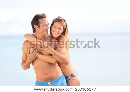 Cheerful 40-year-old couple at the beach - stock photo