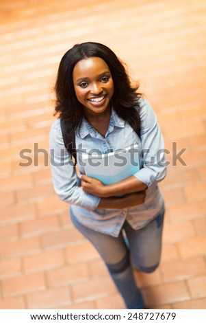 cheerful young african american college girl walking on campus - stock photo