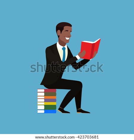 Cheerful young African American in a brown suit and blue tie is with a book in his hands. Student sitting on a pile of multicolored books. Businessman sitting and holding an open book in his hands.  - stock photo