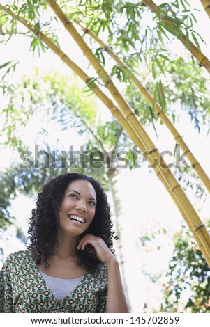 Cheerful young African American woman in bamboo forest - stock photo