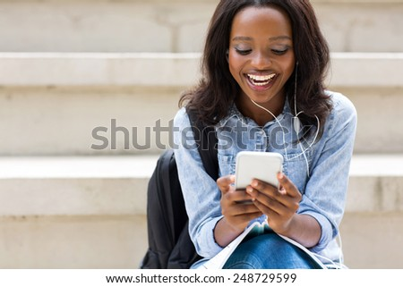 cheerful young african college girl using smart phone listening music - stock photo