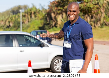 cheerful young african driving instructor presenting a car - stock photo