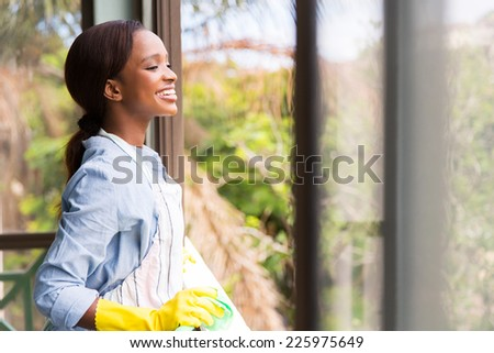 cheerful young african housewife looking through the window - stock photo