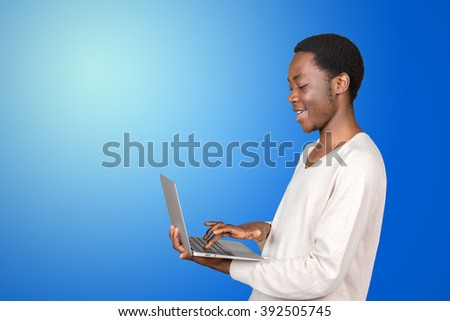 Cheerful young African man using laptop