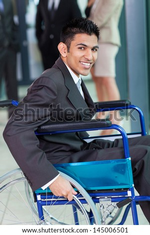 cheerful young Arabic handicapped businessman in office - stock photo