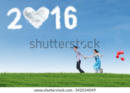 Cheerful young asian couple running on the meadow while holding hands and balloons under clouds shaped numbers 2016 - stock photo