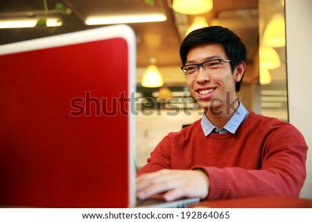 Cheerful young asian man using laptop - stock photo