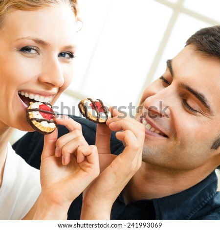 Cheerful young attractive couple eating cakes