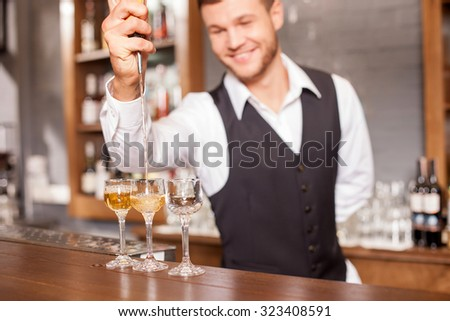 Cheerful young barman is holding shaker and pouring mixed drink into glass. The man is standing at counter and posing in bar. He is smiling - stock photo
