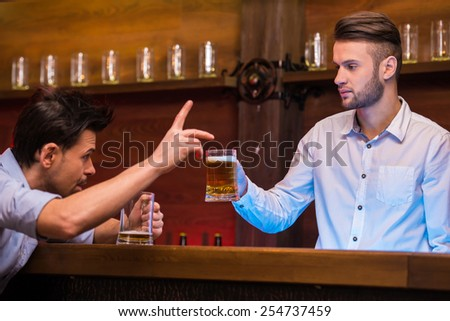 Cheerful young bartender is giving a mug with beer to the customer. - stock photo