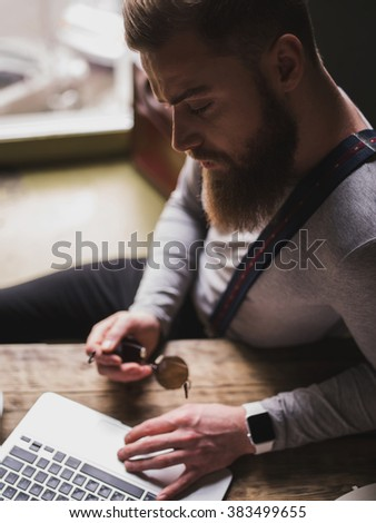Cheerful young bearded guy with a notebook
