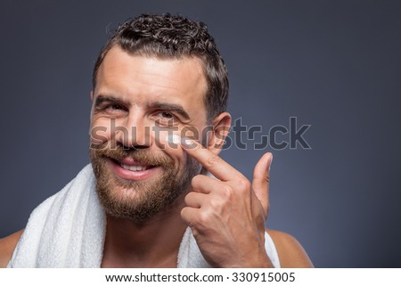 Cheerful young bearded man is applying cream on his face. He is standing and holding white towel on his neck. The man is looking forward and smiling. Isolated and copy space in right side - stock photo