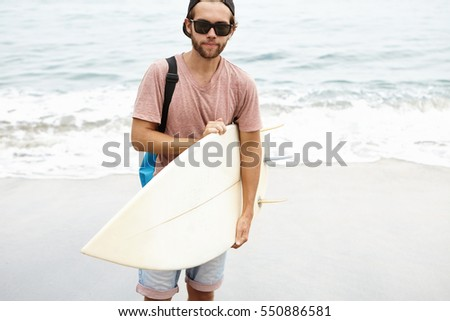 Cheerful young bearded tourist in sunglasses holding bodyboard and looking at camera with pleased smile, happy with his first surf ride during holidays in tropical country, standing on sea shore