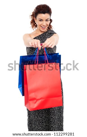 Cheerful young beautiful woman wearing a long black holding shopping bags - stock photo